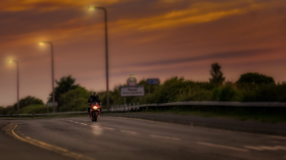 man riding sports bike on road during golden hour