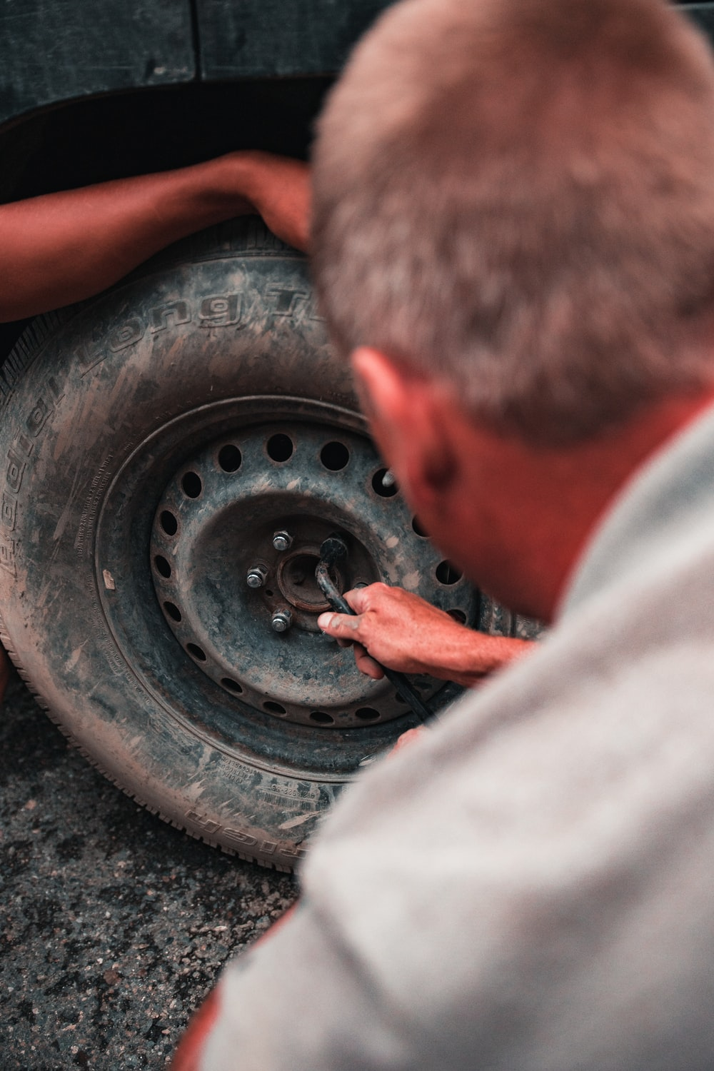man fixing tire of vehicle