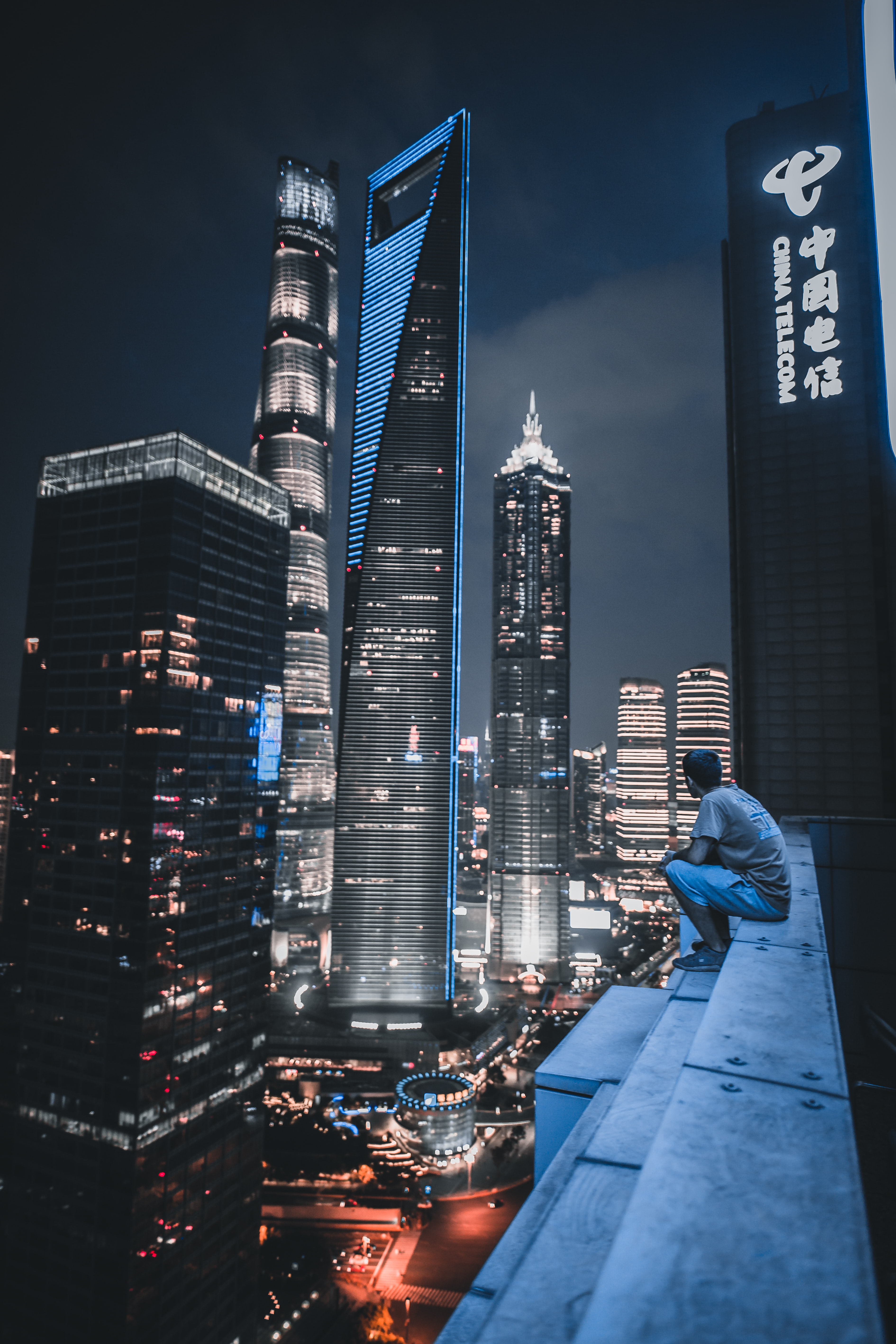 man sitting on roof top viewing city view