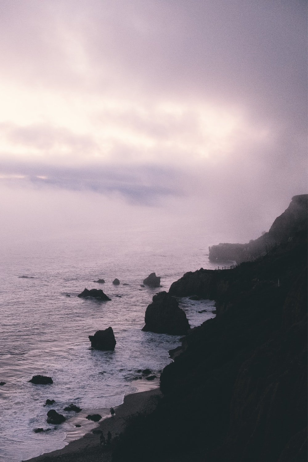 rock formations near sea during foggy weather