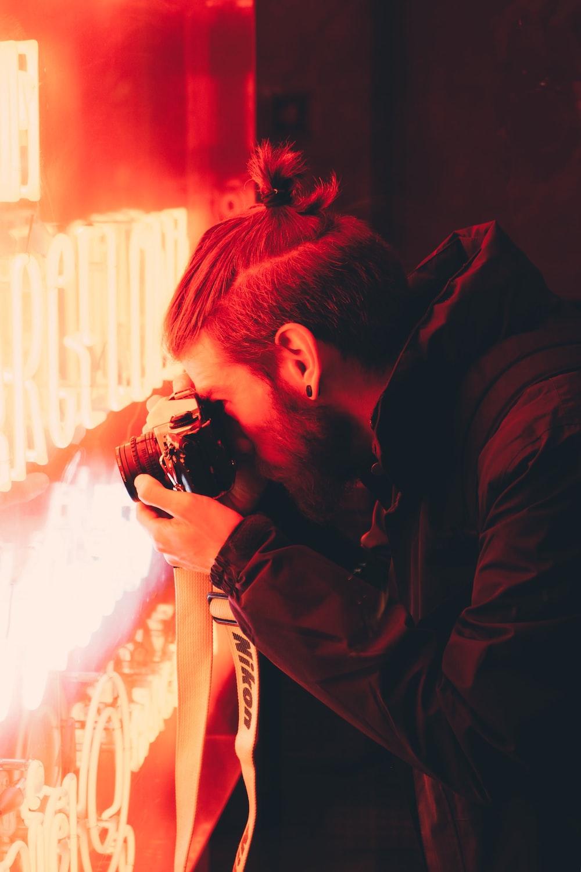 man taking photo of red LED neon signage