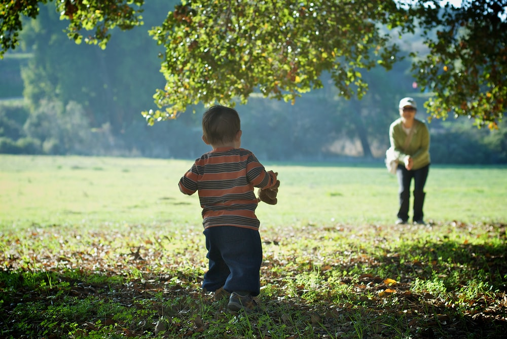 focus photography of boy standing near tree