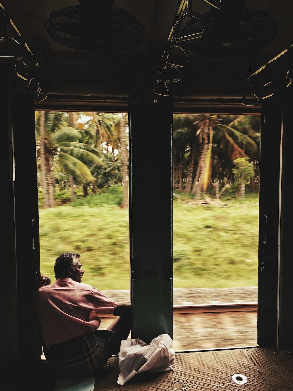 man sitting on doorway near coconut trees