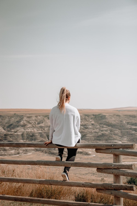 woman sitting on brown wooden railings