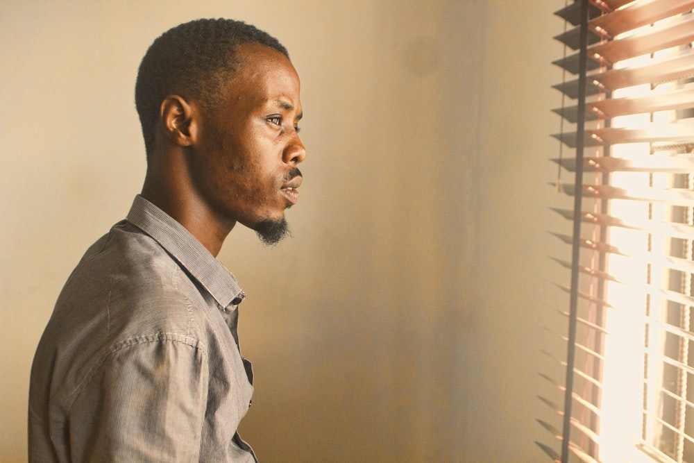 man standing near window with blinds