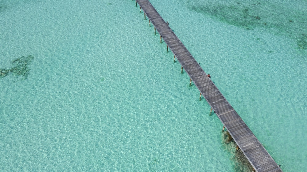 brown wooden dock on blue water during daytime