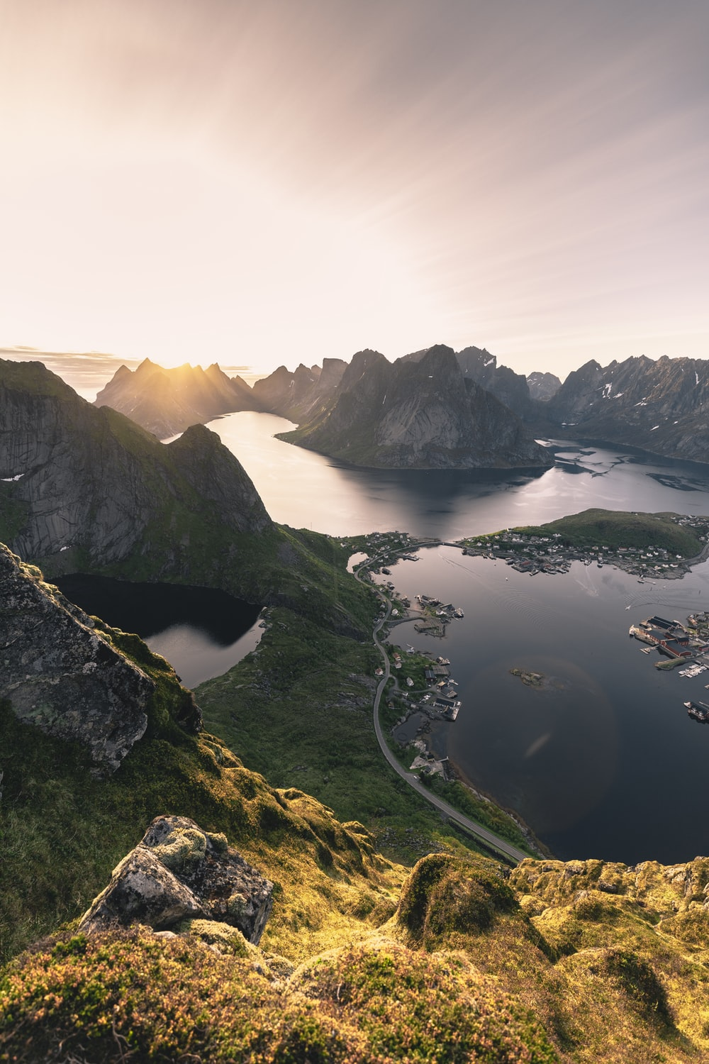 aerial photo of mountains surrounded with body of water during golden hour