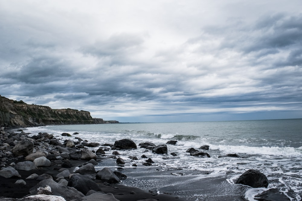 seashore beside rocks under white and gray clouds