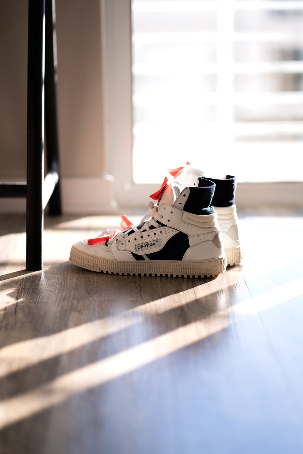 pair of white-and-black high top sneakers on floor