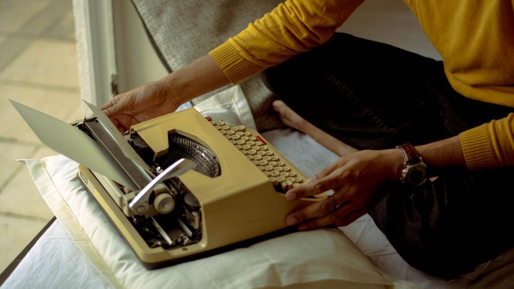 person using yellow typewriter