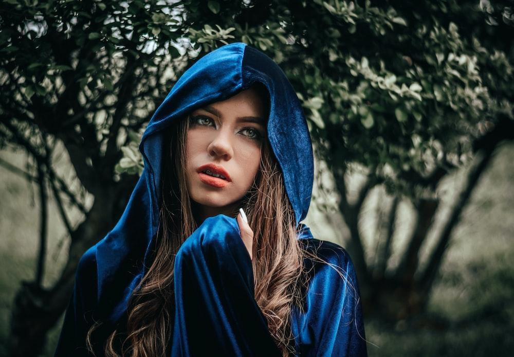 woman in blue hoodie near green tree