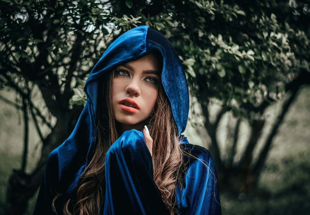 woman in blue hoodie near green tree