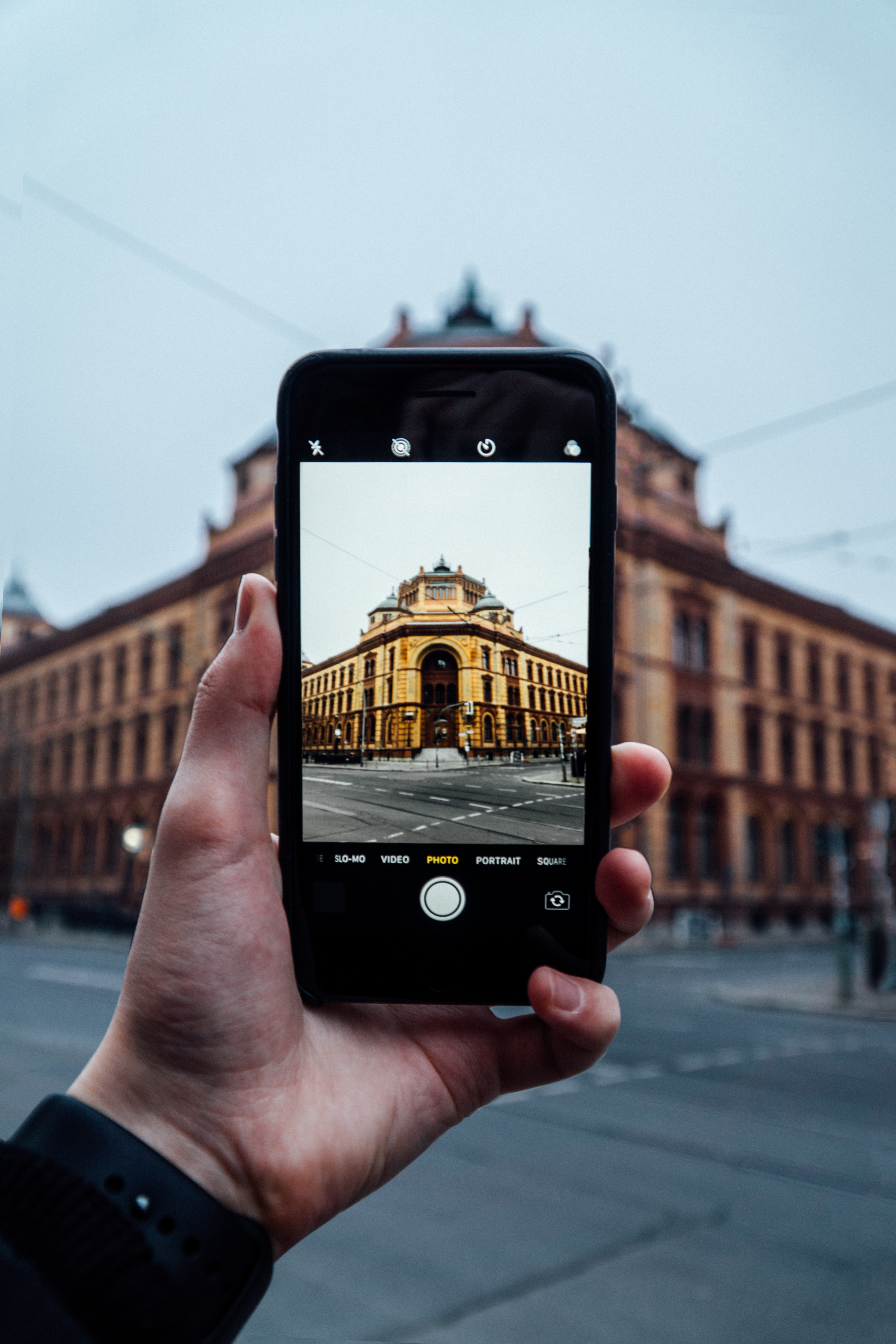 black smartphone with brown concrete building photo in screen during daytime