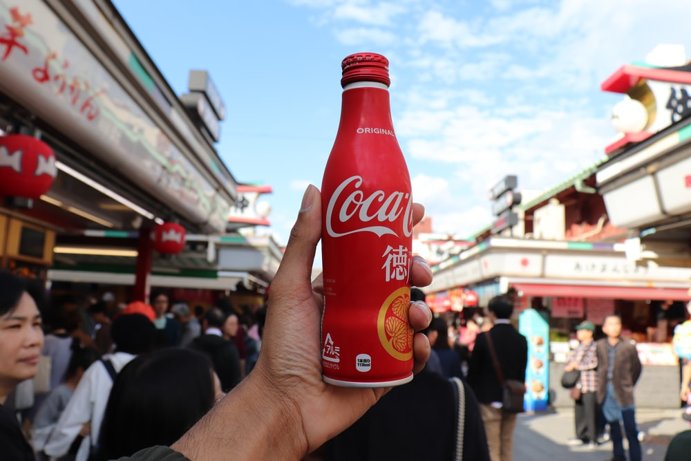 person holding red coca cola bottle near crowd
