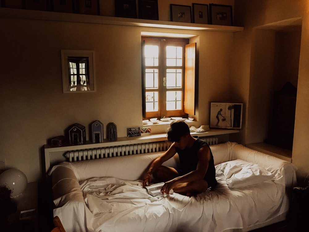 man sitting on bed beside opened window