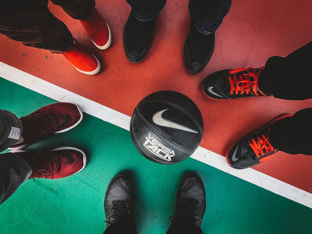 five persons standing in front of black and white Nike basketball