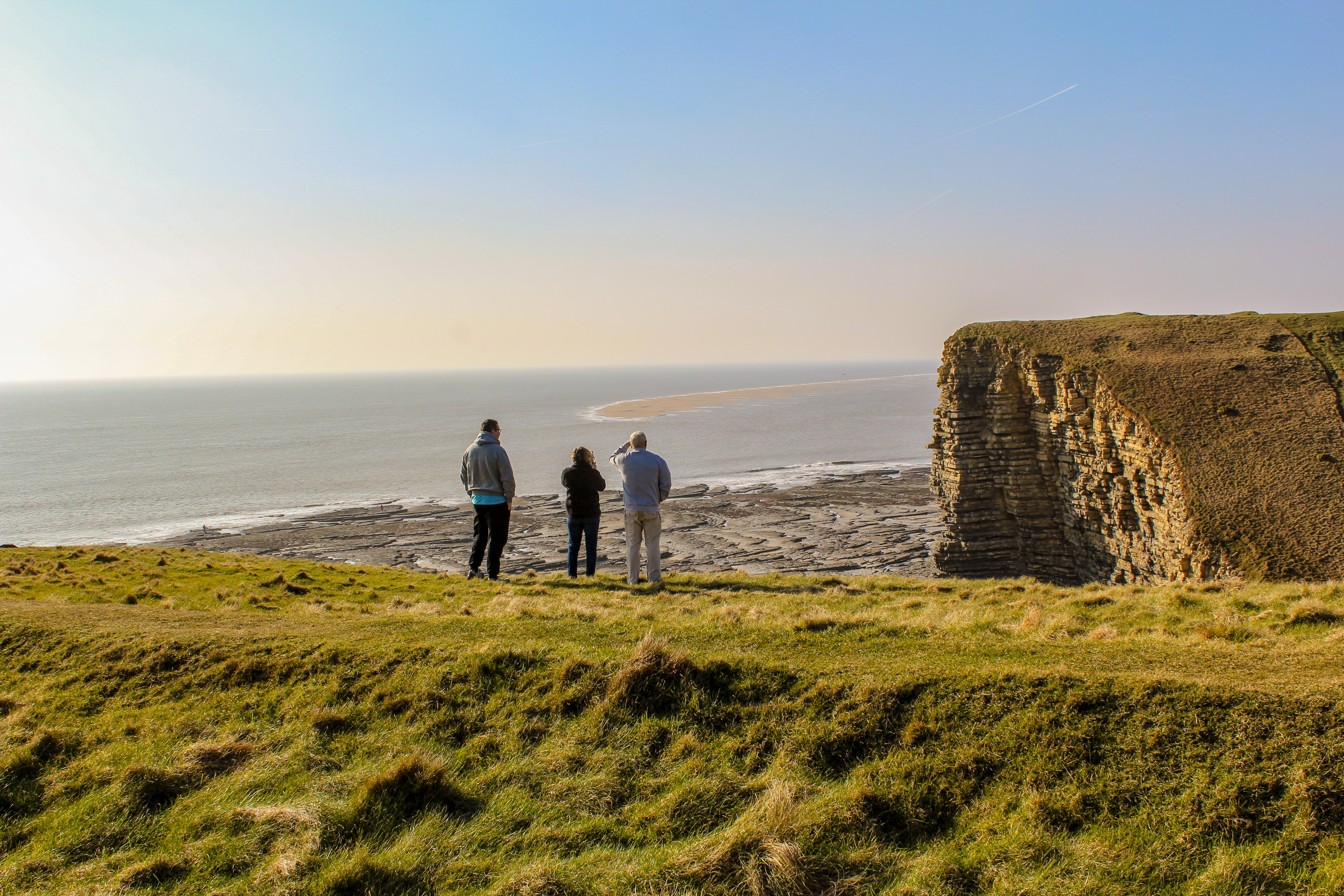 three people standing on shore