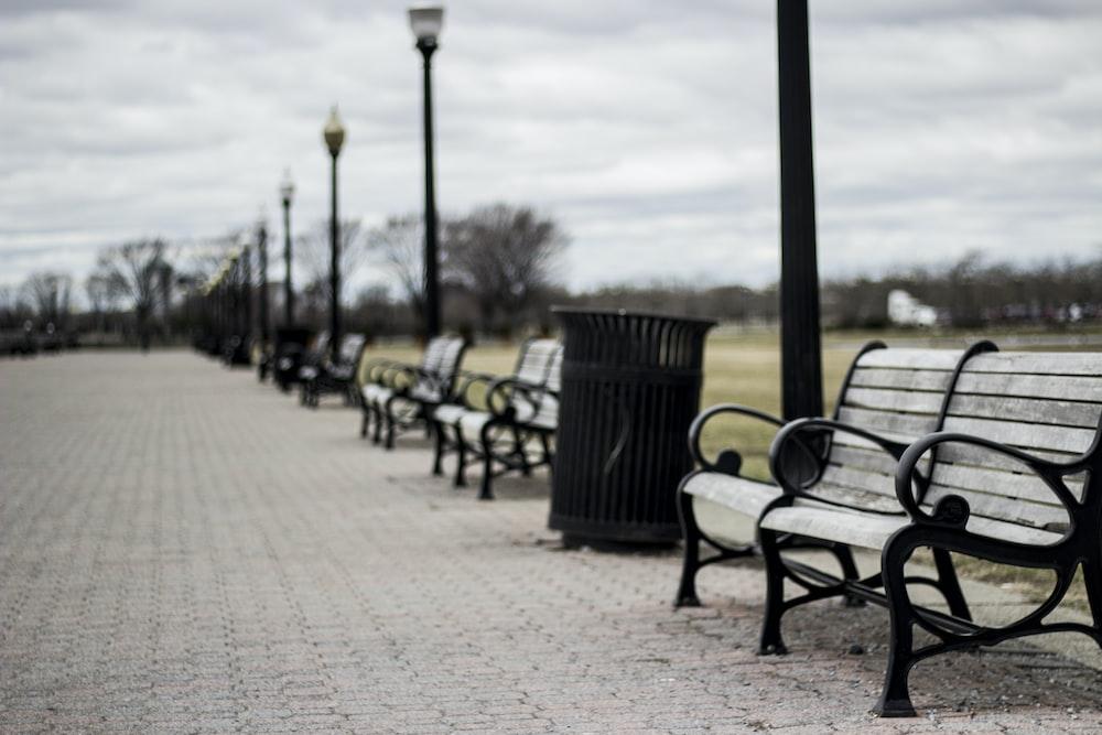 empty grey bench under grey clouds