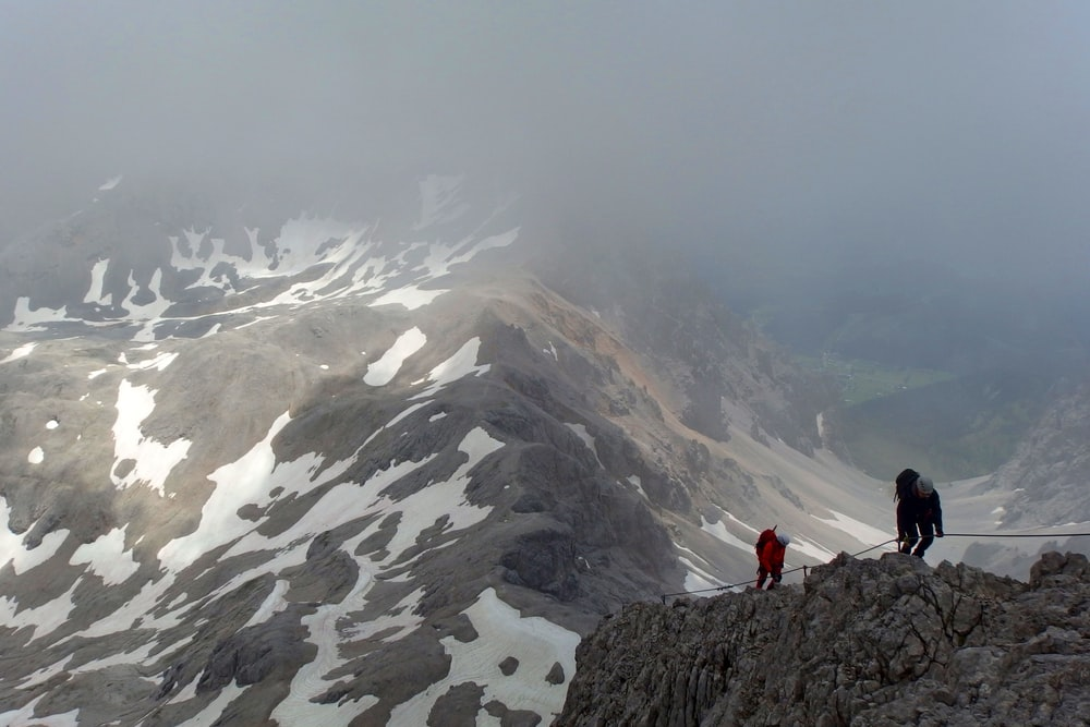 two person hiking on gray mountain
