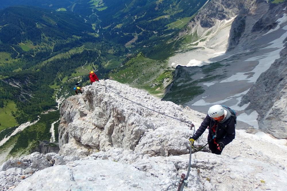 three people climbing on rock mountain during daytime