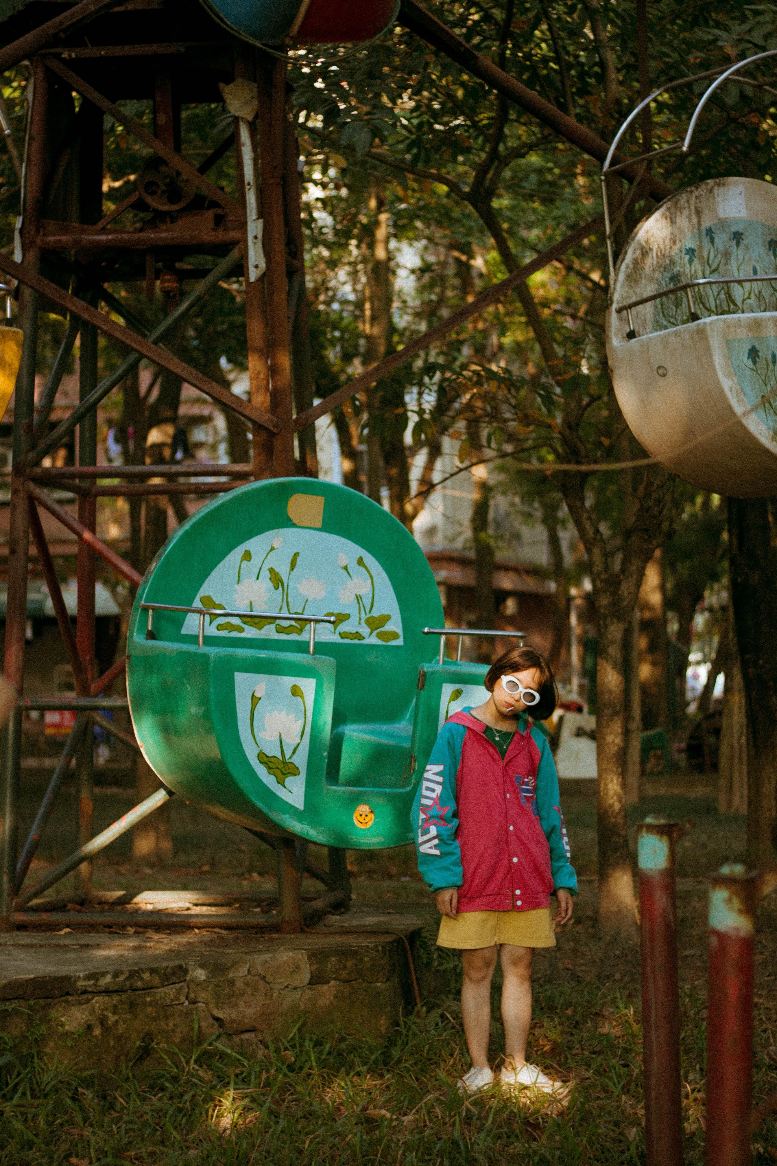 girl standing in front of green ferris wheel