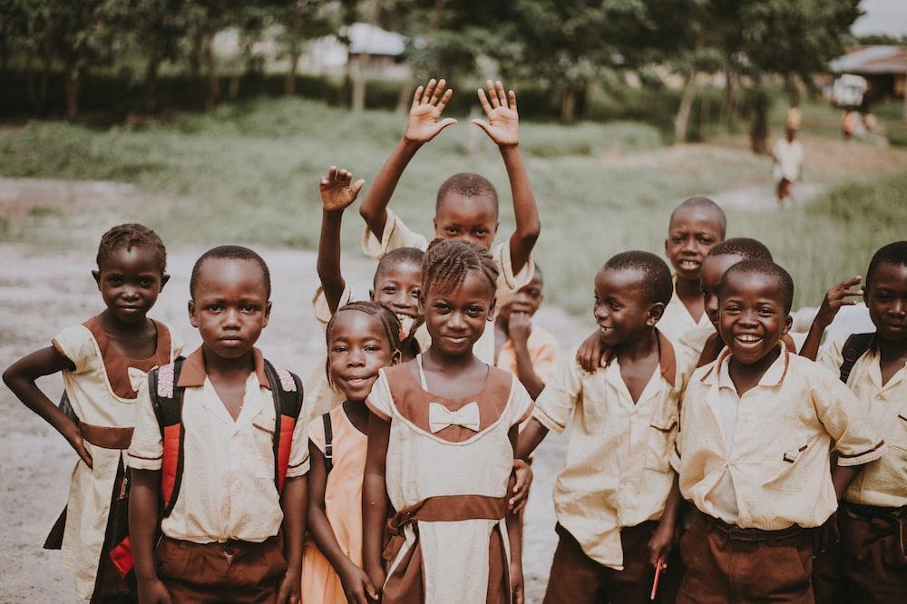 group of children standing in green field