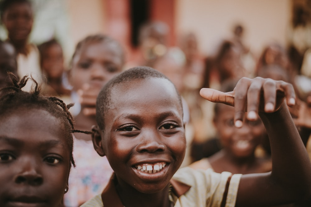 boy in brown collared top smiling and surrounded by children