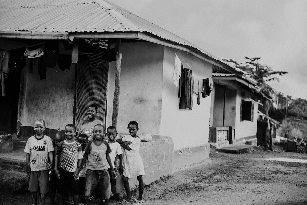 grayscale photo of kids outside house