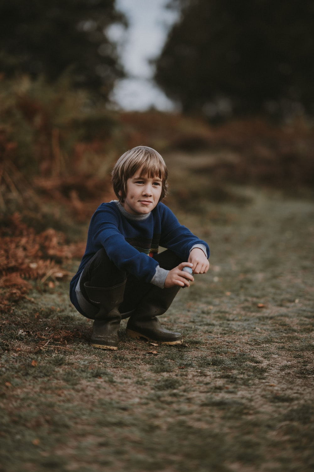 boy in blue sweater squatting down on brown pathway