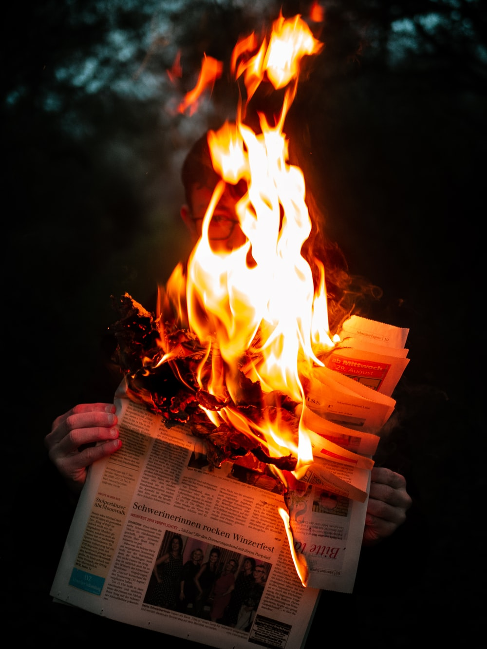 Homepage Newspaper: Person Holding Burning Newspaper Photo