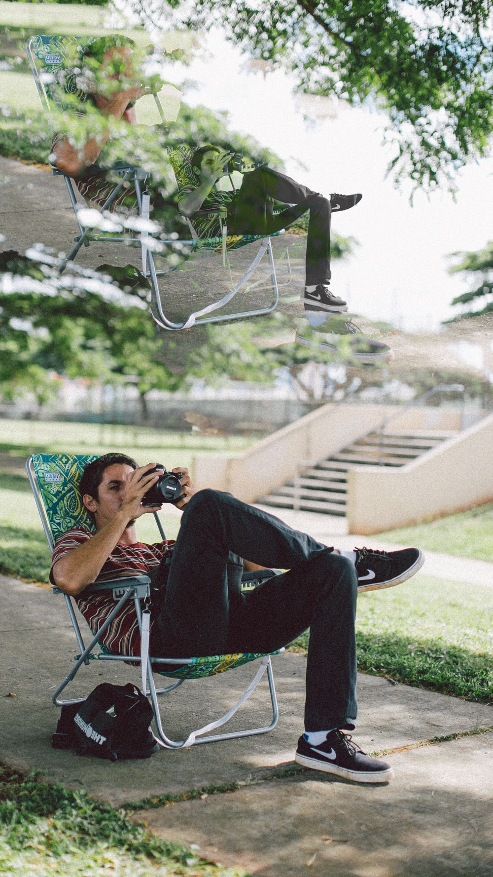 man sitting on folding chair using DSLR camera