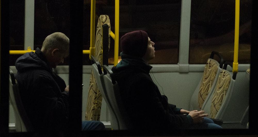 men sitting on bus seat