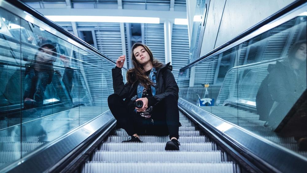 woman sitting on escalator