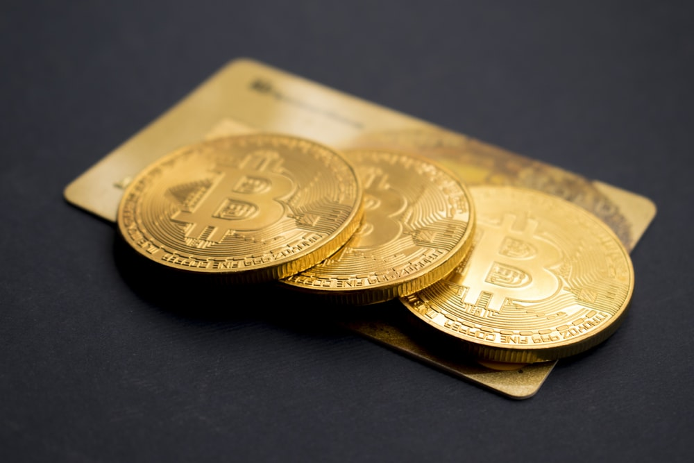 three round gold-colored Bitcoin tokens