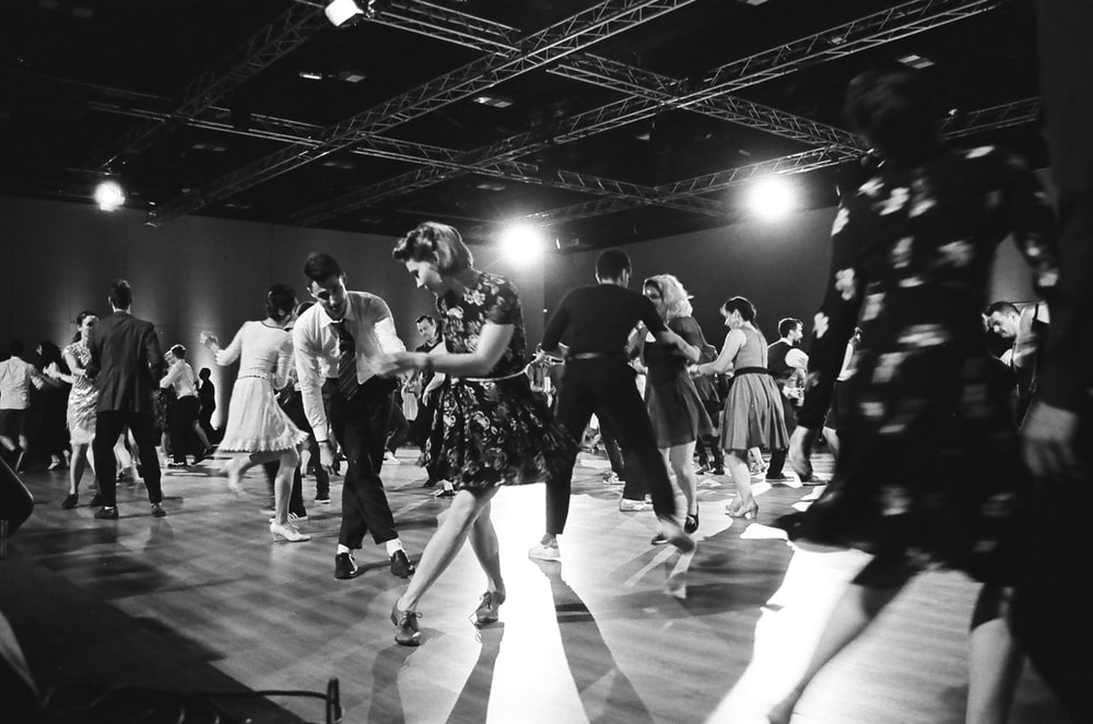 grayscale photography of people dancing on stage