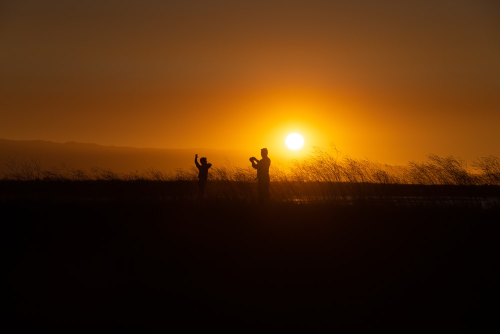 silhouette of two people on grassfield playing under orange sky