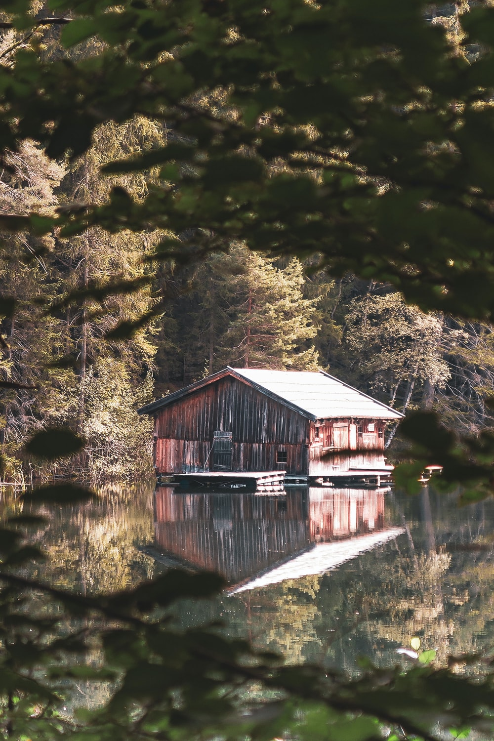 brown wooden house near body of water and trees