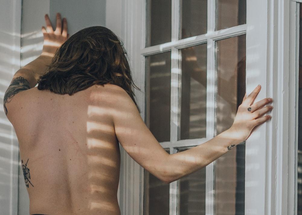 topless woman standing near window