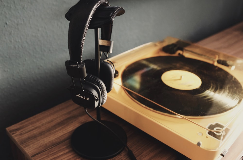 black and beige turn table beside black headphones
