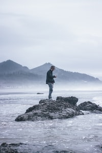 man standing beside body of water during daytime