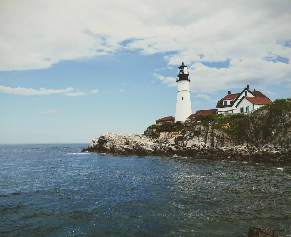 lighthouse on rock formation near beach