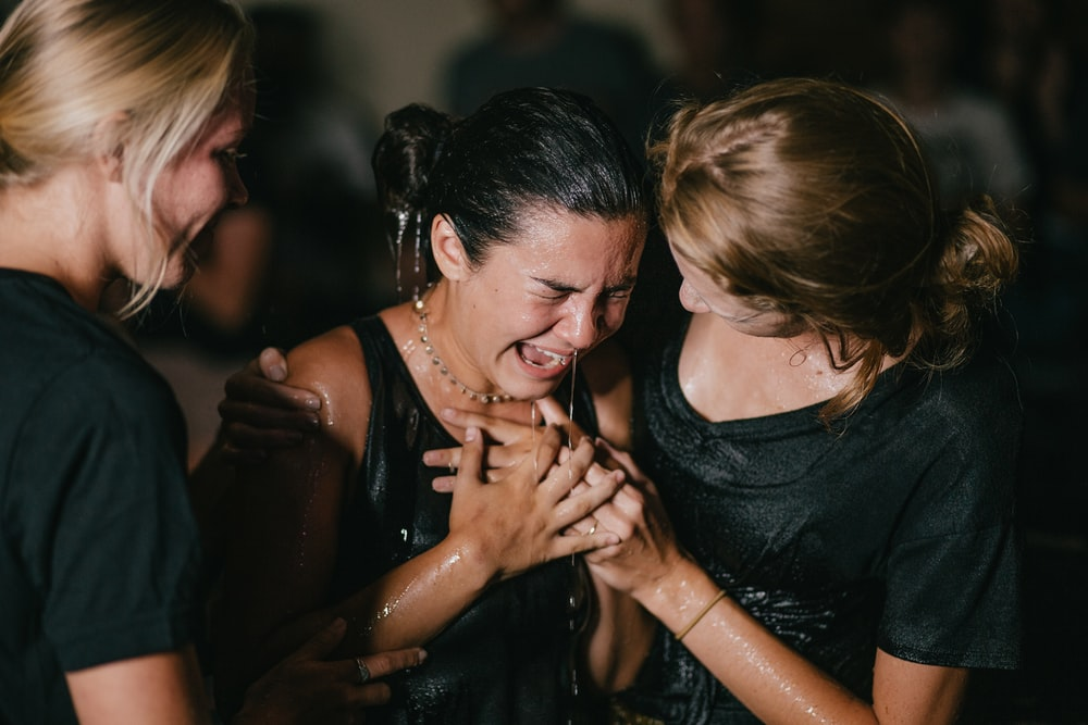 crying woman between two women in black shirts