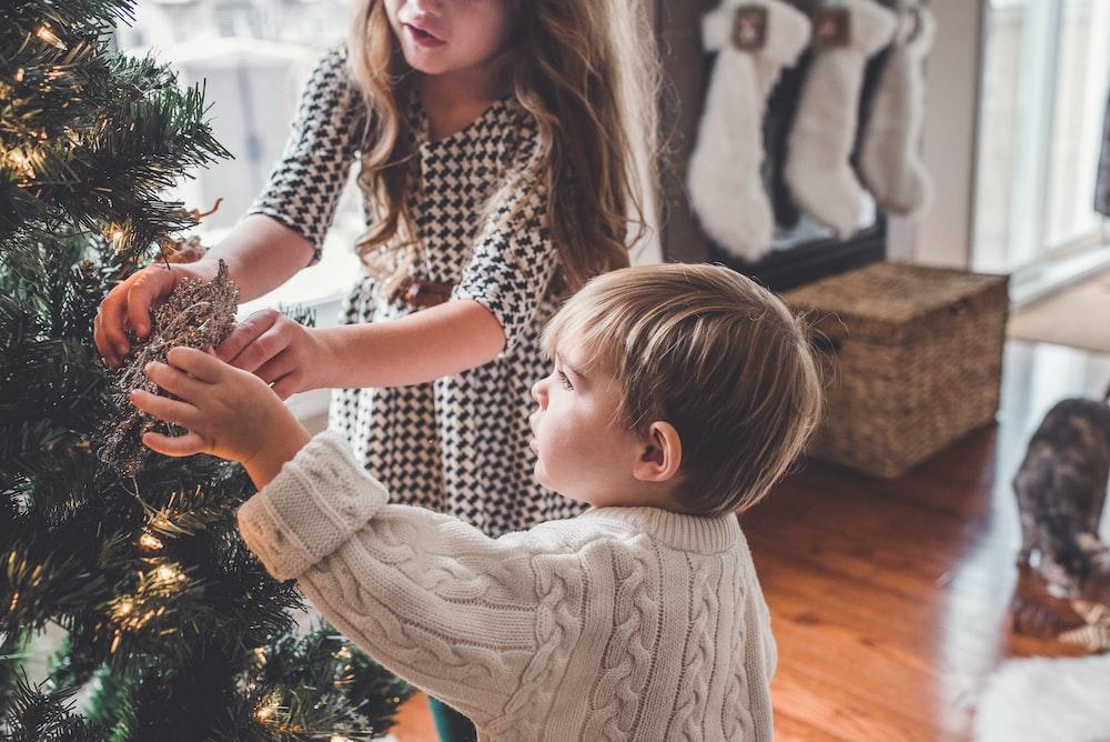 boy and girl decorating Christmas tree inside room