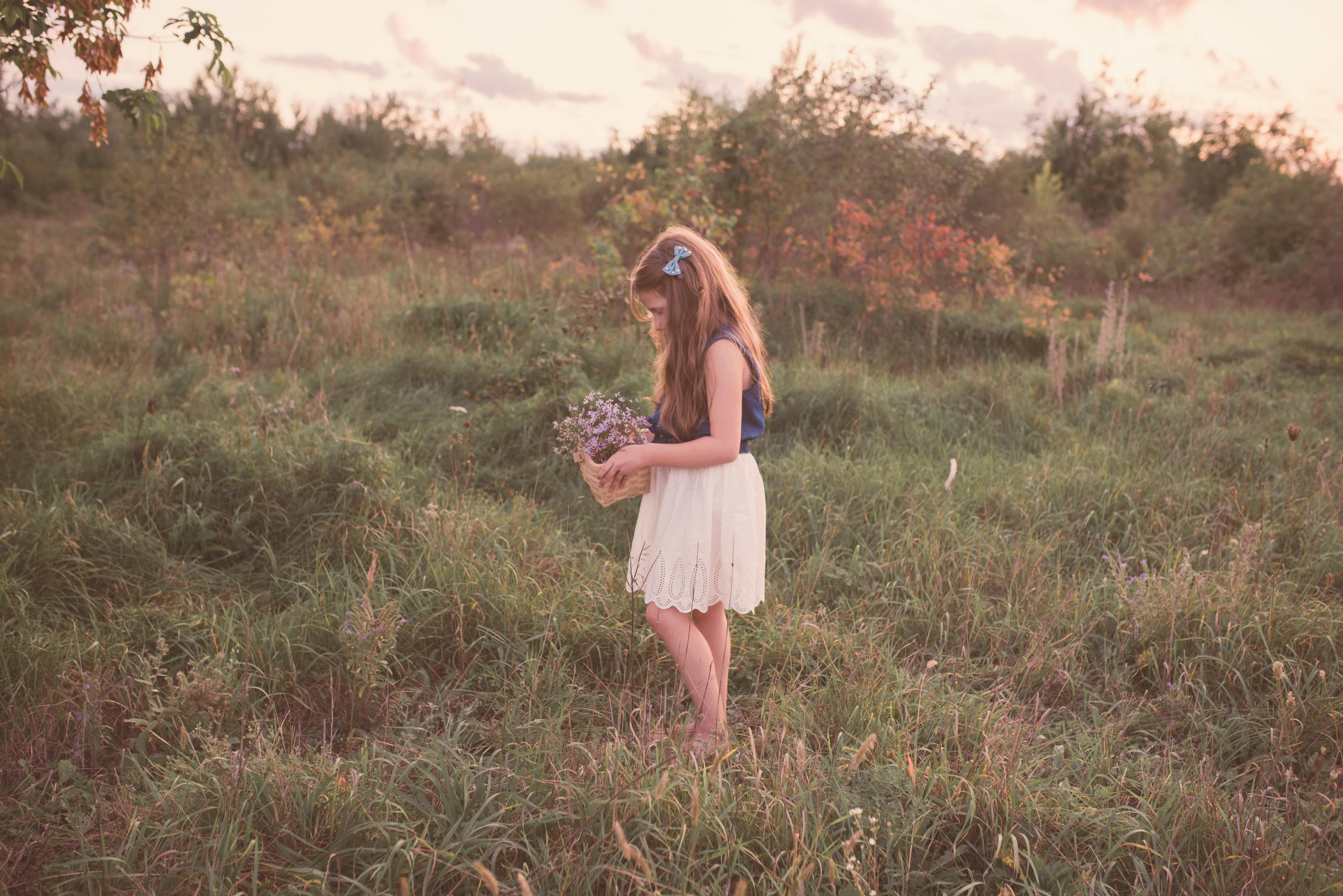 girl holding basket of flower standing on grass field