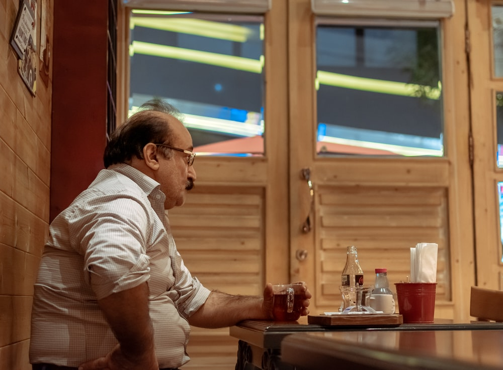 man sitting near the table while holding glass mug