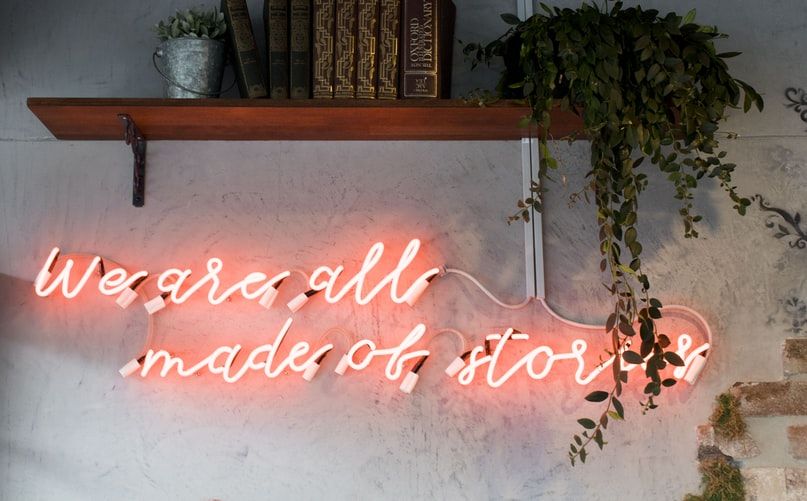 "A photo of a wall with a neon sign that says ""we are all made of stories"""
