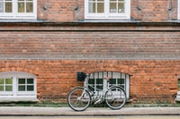 bicycle parked beside brown wall