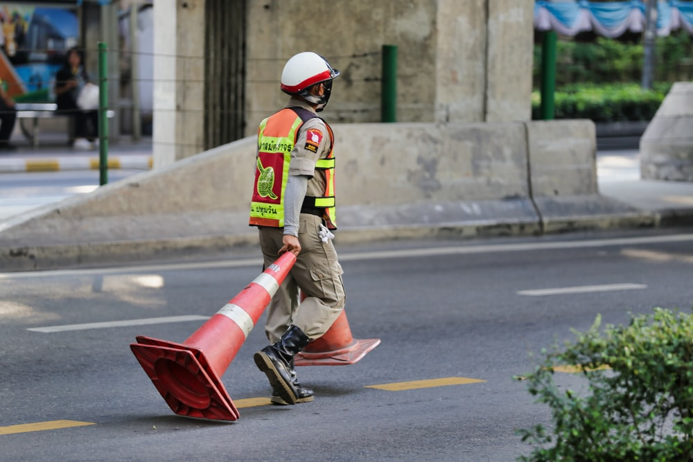 man pulling parking cones along road