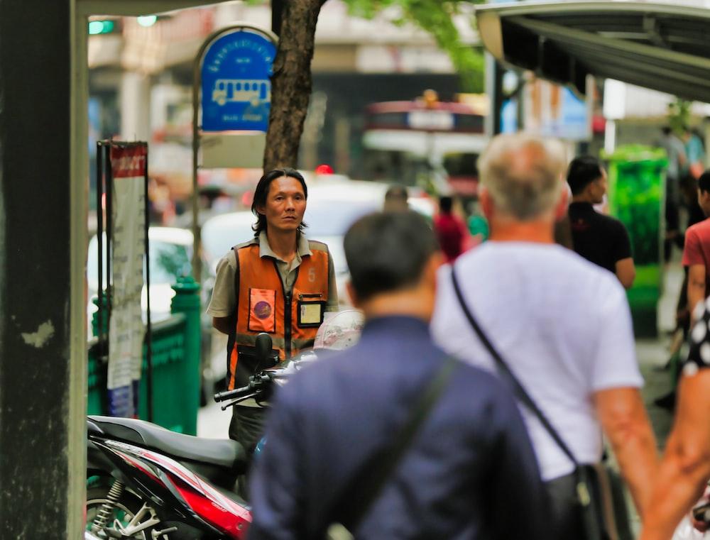 people walking beside man in orange vest