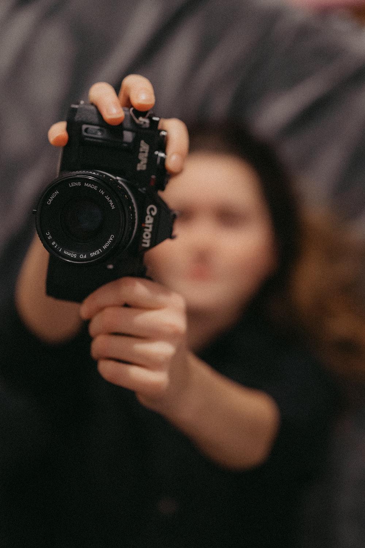 woman holding Canon film camera